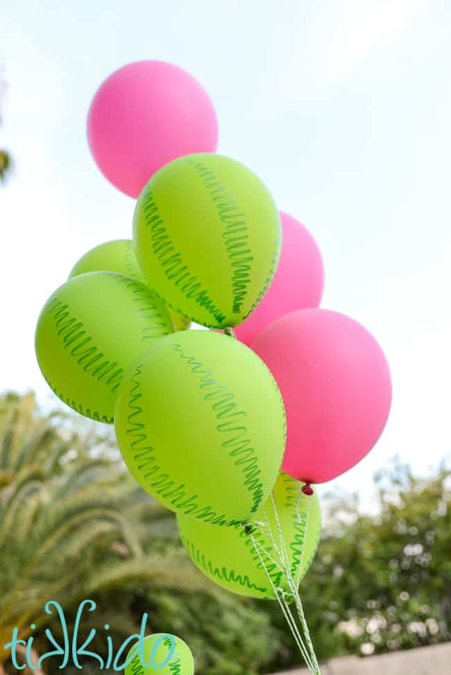 bunch of pink and green balloons the green balloons have a watermelon rind pattern drawn on them