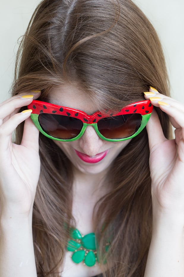 woman looking down and wearing sunglasses painted with watermelon pattern