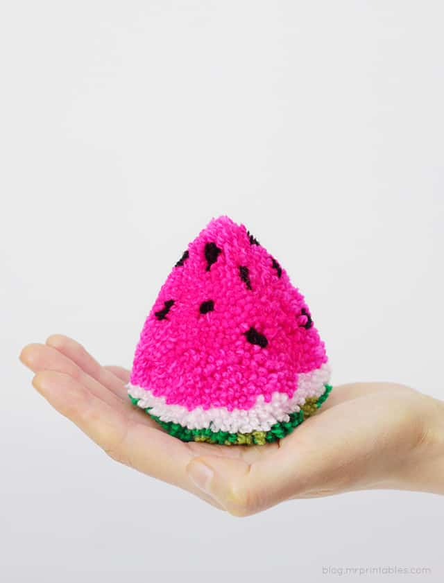 hand holding a green white and pink wedge shaped yarn pom pom