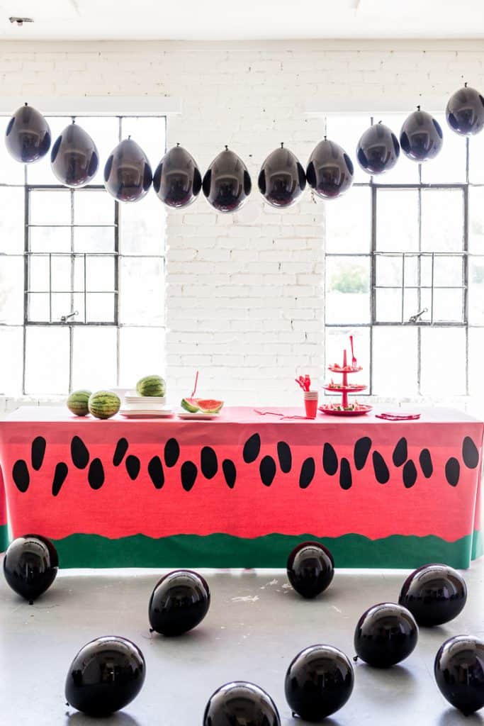 Party room with a long table covered in a watermelon print table cloth and black seed balloons everywhere