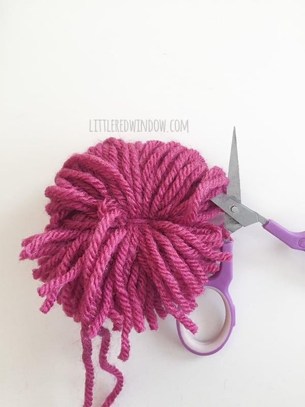 pair of purple scissors cutting the loops on the pink yarn bundle
