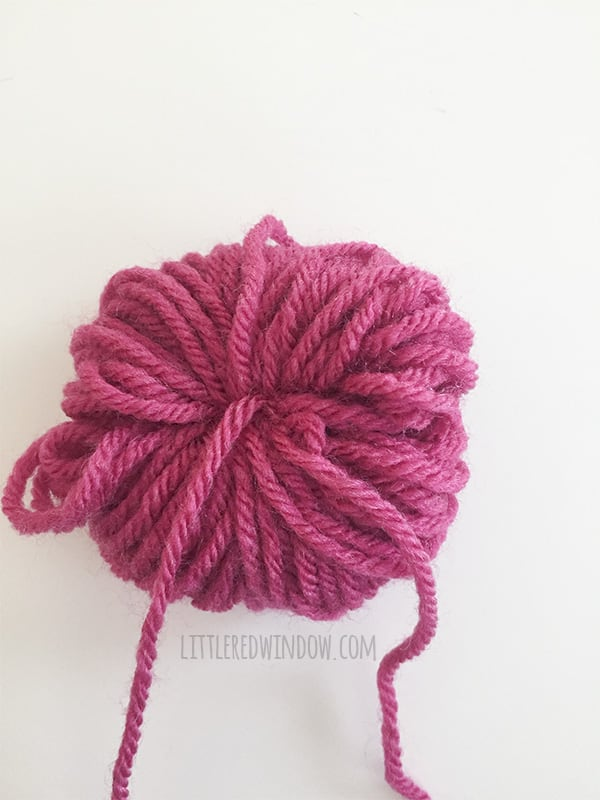 a pink yarn bundle tied with yarn around the center