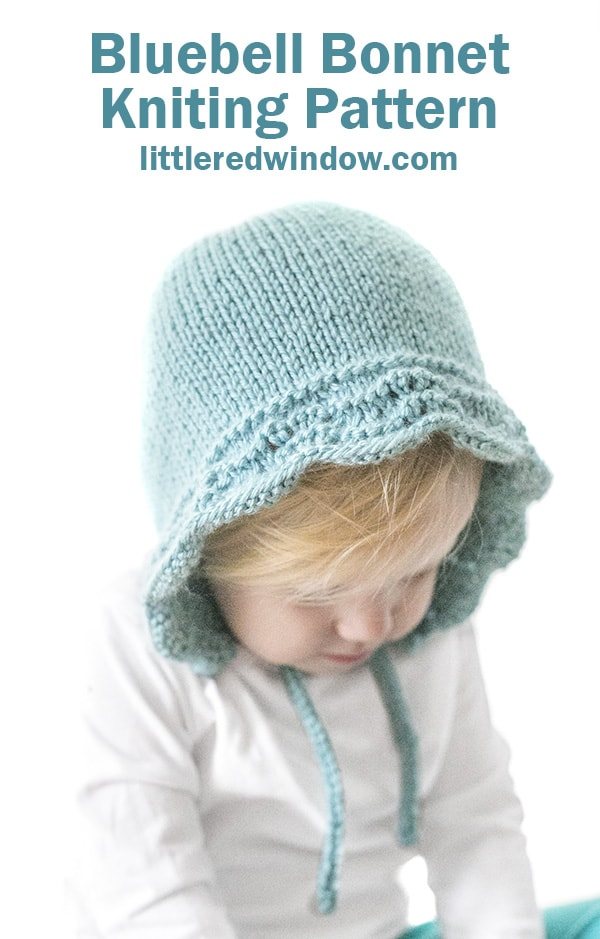 baby girl in white shirt wearing light blue knit bonnet with wavy edge looking down at her hands