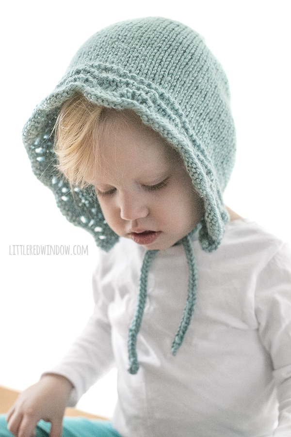 baby girl with white shirt and light blue knit bluebell baby bonnet with chin ties looking down