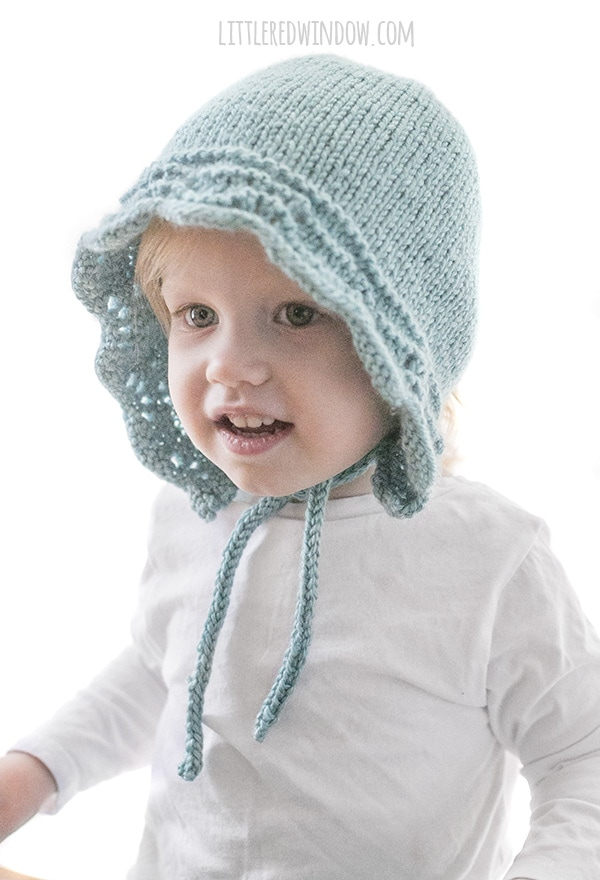 smiling baby with knit light blue baby bonnet with knit chin ties