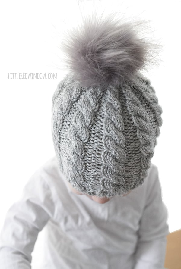 Twist Cable Hat Pattern for newborns, babies and toddlers! This cute cable pattern and faux fur pom pom will look adorable on your little one this winter, time to start knitting! | littleredwindow.com