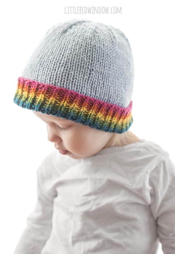 Cute baby wearing Rainbow Brim Hat knitting pattern!