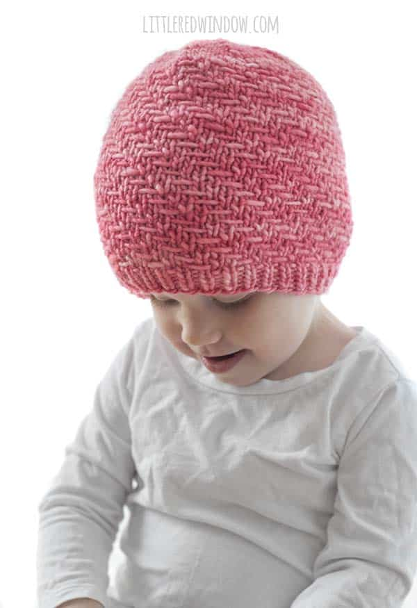 toddler in white shirt wearing coral pink knit hat with diagonal weave stitch pattern looking down