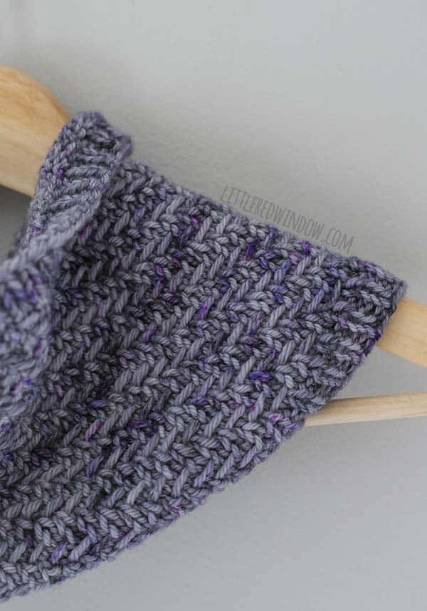 Closeup of the herringbone stitches on the hazel herringbone cowl hanging on a light wood hanger in shades of lavender and purple yarn in front of a white background