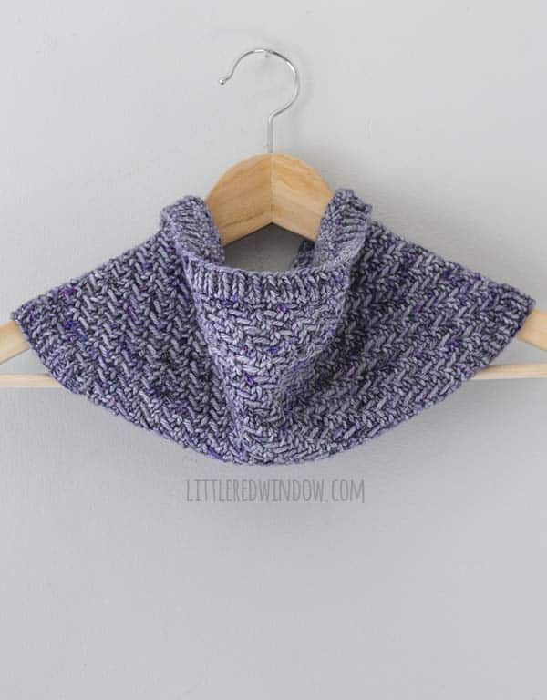 front view of purple knit cowl hanging on a light wood hanger in front of a light gray wall