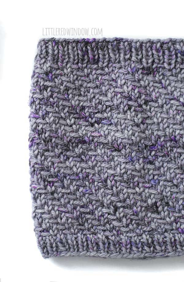 Closeup of the herringbone stitches on the hazel herringbone cowl in shades of lavender and purple yarn in front of a white background