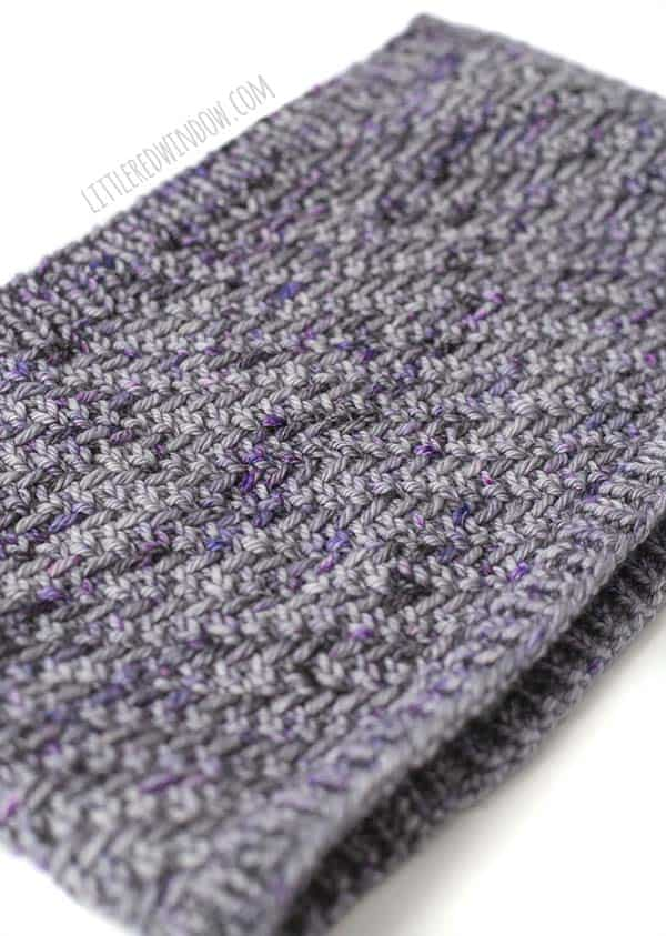 Closeup of the herringbone stitches on the hazel herringbone cowl laying flat diagonally in shades of lavender and purple yarn in front of a white background