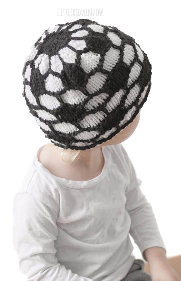 girl in white shirt wearing a knit hat that looks like a soccer ball and looking back over her left shoulder