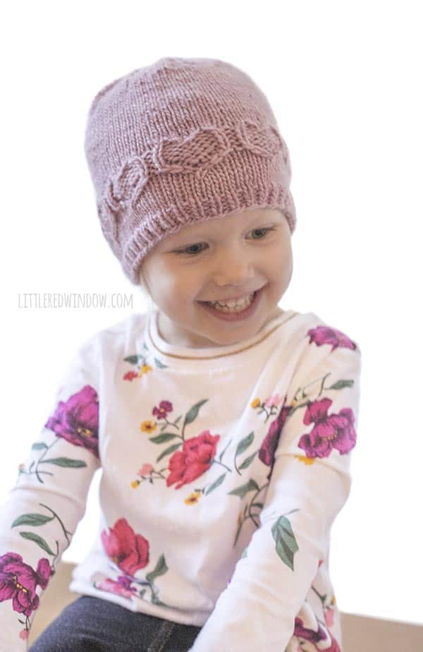 Happy girl wearing Valentine Sweetheart Hat knitting pattern!
