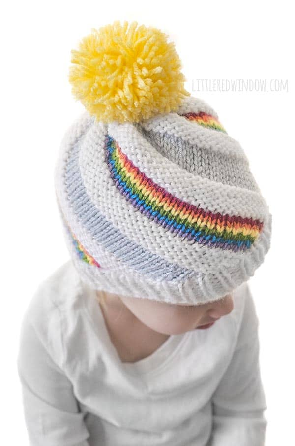 The Rainbow Swirl Hat knitting pattern looks cute from the brim to the bright yellow pom pom on top!