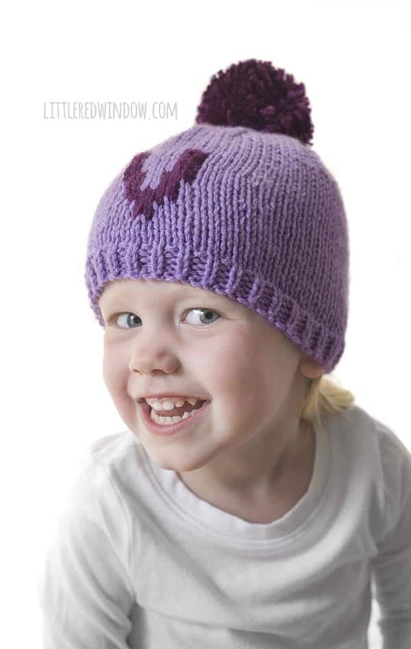 Little girl smiling and wearing purple letter V Monogram hat!