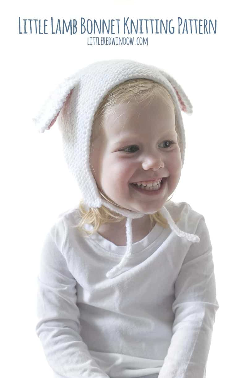 Smiling little girl wearing a white bonnet with lamb ears