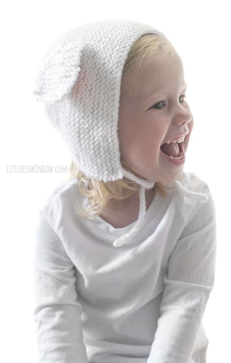 Laughing little girl wearing a white bonnet with lamb ears