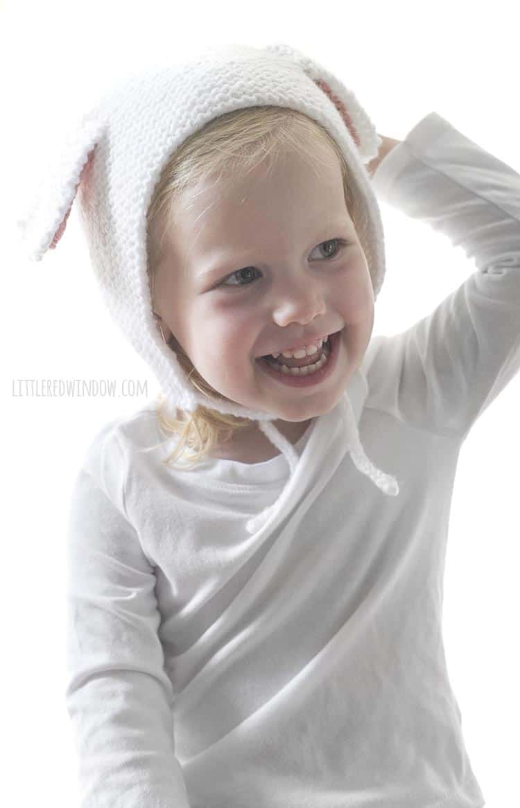 Smiling little girl holding one hand on top of her white lamb bonnet