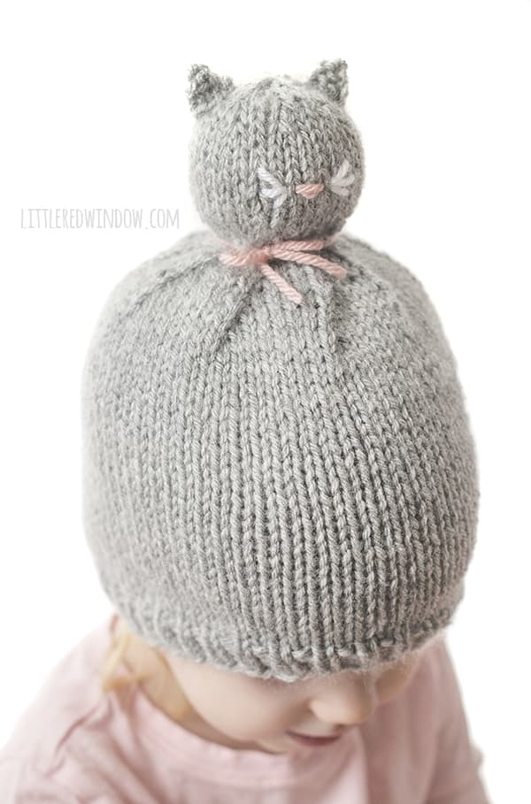 The Kitty Cat Pom Pom Pet Hat knitting pattern has a sweet embroidered pink nose and adorable little whiskers!