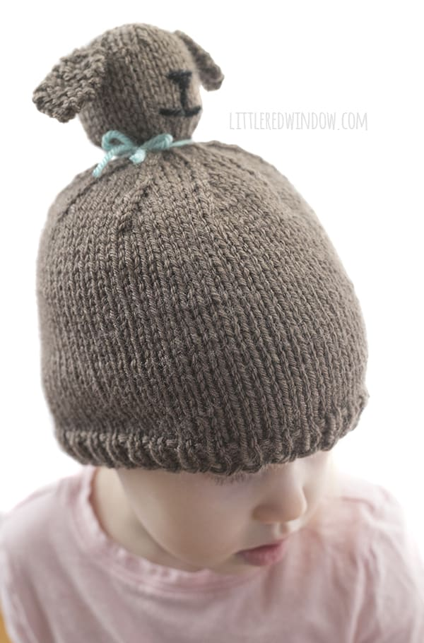 Little girl loves showing off the Puppy Dog Pom Pom Pet Hat knitting pattern. This cute little guy even has an adorable puppy nose and cute floppy ears!