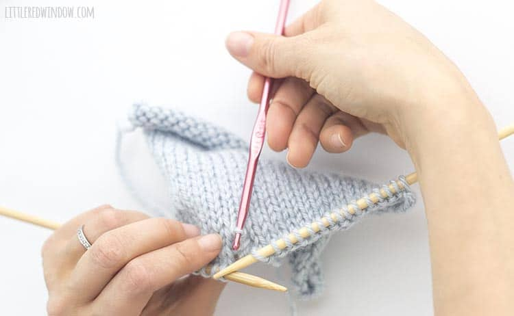 To fix a dropped purl stitch, insert a crochet hook in the live stitch from back to front
