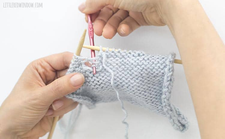Grab the loose yarn and pull through to the back to fix a dropped purl stitch