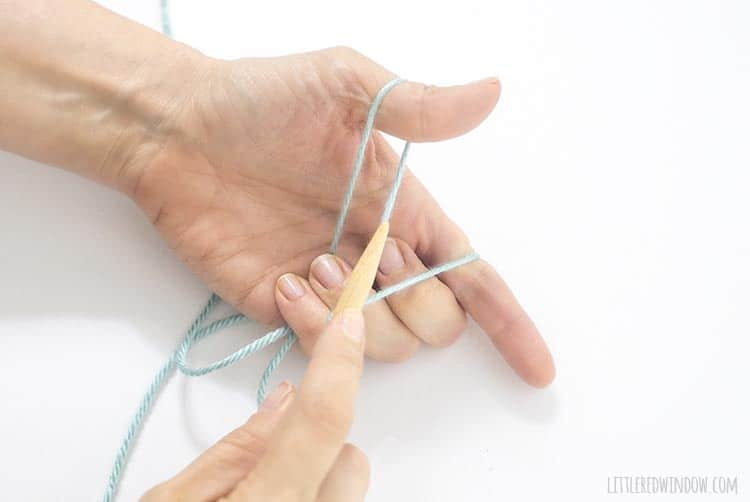 To begin a long tail cast on, put the needle through the loop of yarn going around your thumb