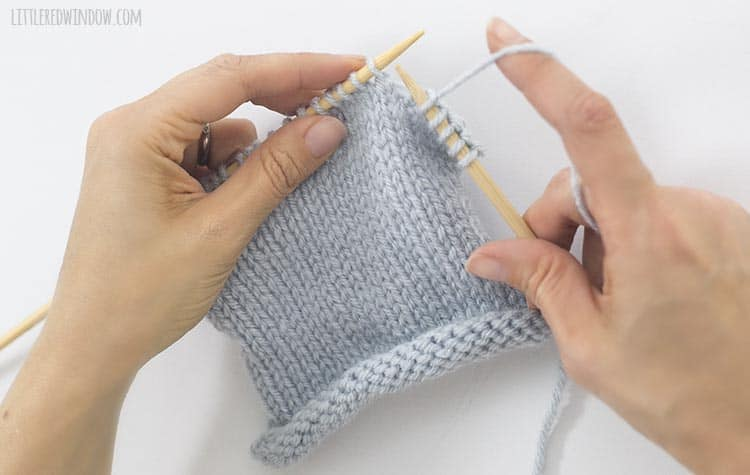 To knit a knit stitch, hold the yarn behind the work