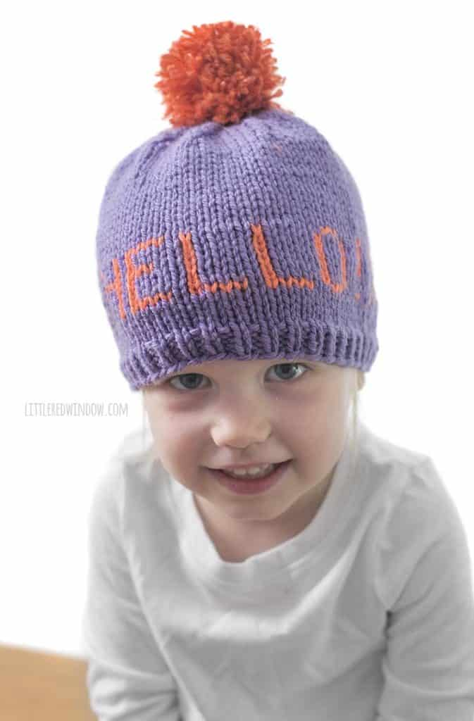 "Cute baby wearing a Greetings baby hat that says ""hello"""