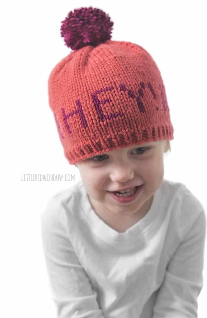 "Cute baby wearing a Greetings baby hat that says ""hey!"""