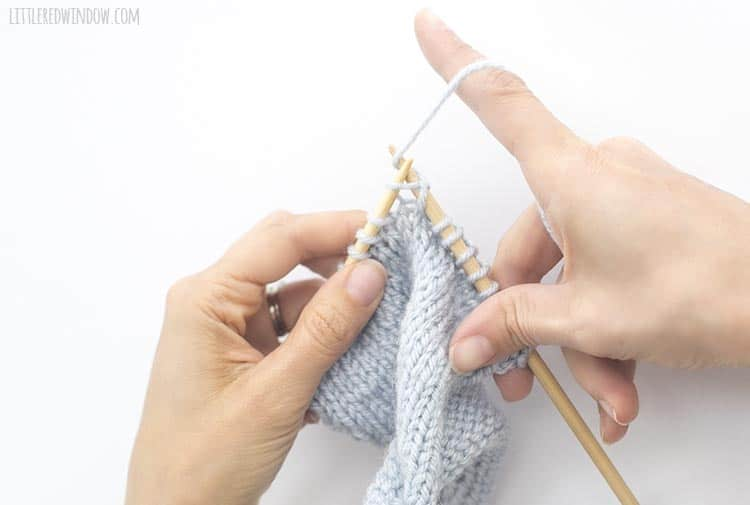 To complete a yarn over, continue on knitting the next stitch while still holding the yarn to the back of the work