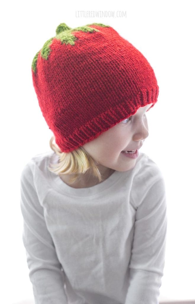 little girl wearing red knit tomato hat and looking to the right
