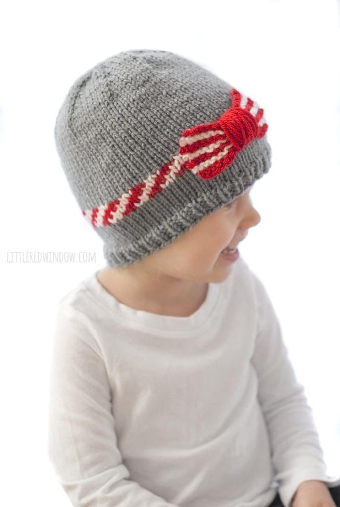 The candy cane bow hat knitting pattern has a red and white stripe around the brim and a fun red and white striped bow to top it all off!
