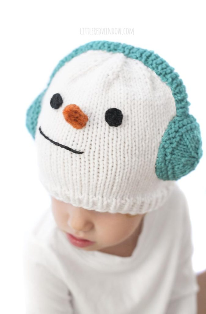 This cute and cozy snowman hat knitting pattern is complete with warm earmuffs, a carrot nose and a sweet smile, it's the perfect winter knitting project to knit for you baby or toddler!