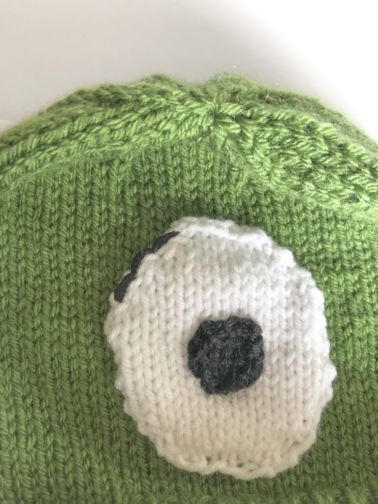 Thread black yarn on a yarn needle and stitch a few stitches along the top of the eye to start the monster's eyelashes