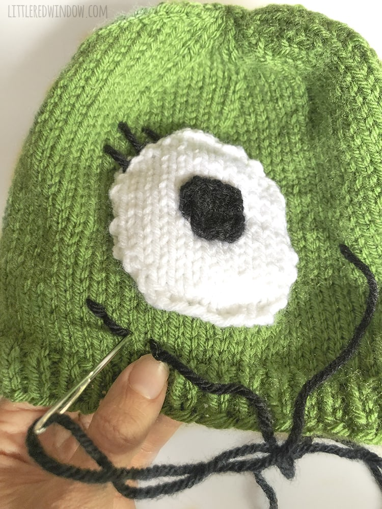 Thread black yarn on your yarn needle and stitch a smiling mouth on your monster hat!