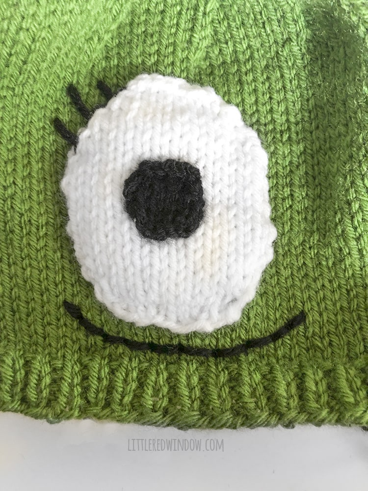 The monster baby hat is a cute and friendly monster face with one eye and a big smile!
