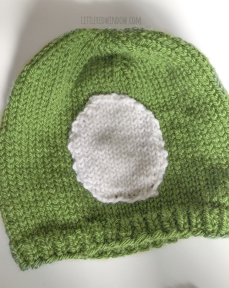 To assemble your monster hat, stitch the white part of the eye to the front of the hat