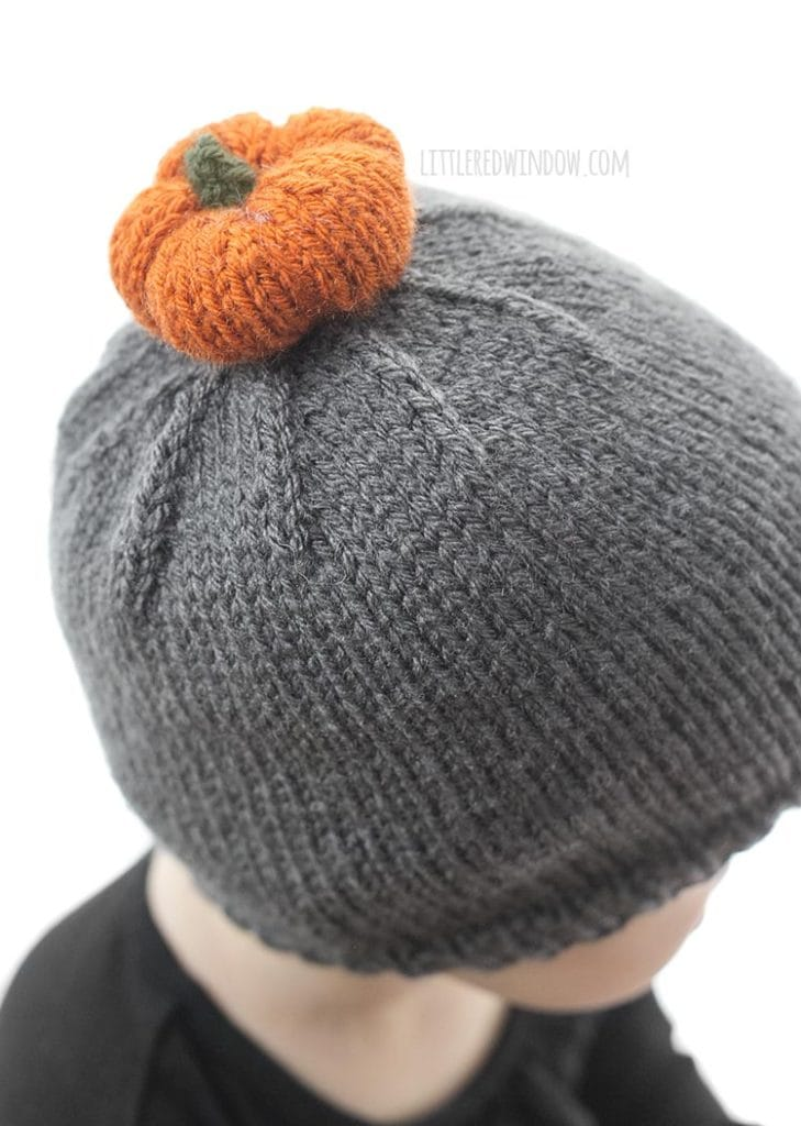 Adroable orange knit pumpkin on top of a cute baby pumpkin patch hat