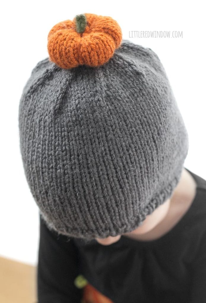 The pumpkin patch hat knitting pattern has a little (adorable) knit pumpkin pom pom on top! It's the perfect fall hat to knit for your baby or toddler!