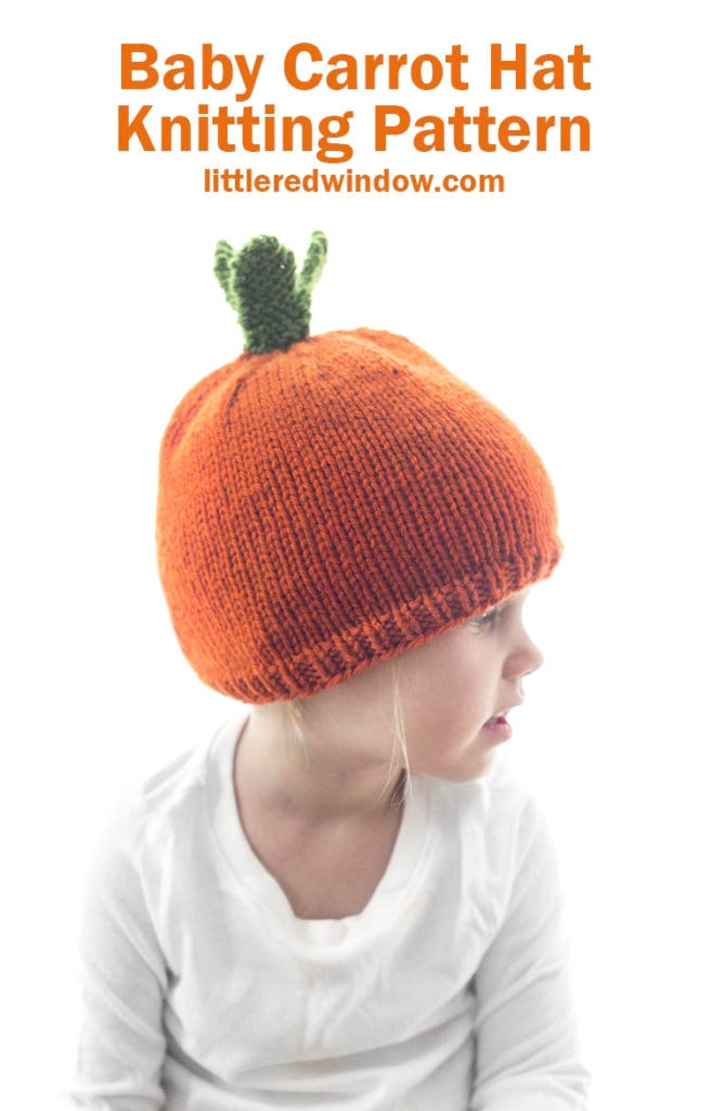 little girl in white shirt wearing an orange carrot hat with green leaves on top looking off to the right
