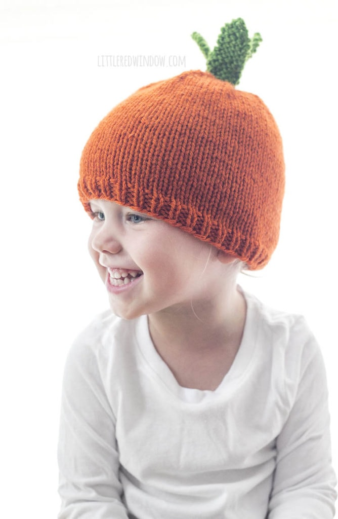 smiling girl wearing orange hat that looks like a carrot and looking forward and to the left