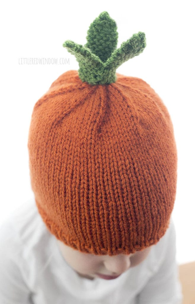 top view of orange and green knit carrot hat