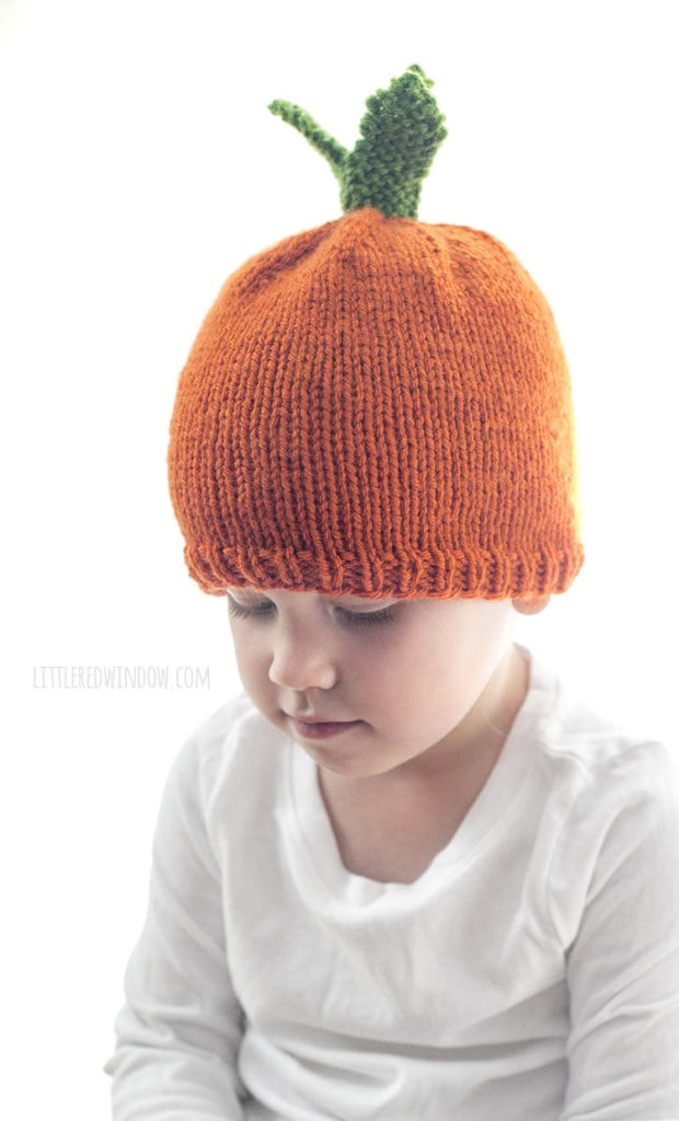 little girl wearing carrot hat and looking down at her hands