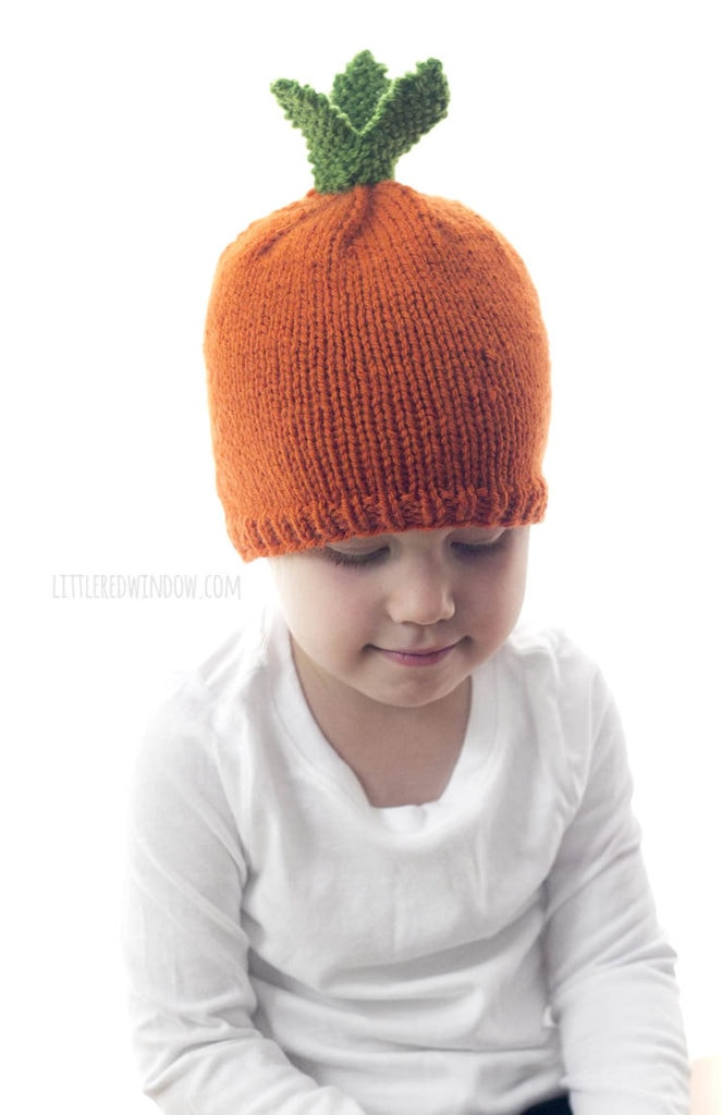 little girl looking down at her hands while wearing a white shirt and orange hat that looks like a carrot