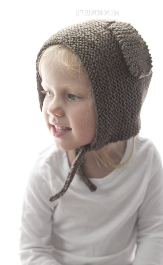 The puppy dog bonnet knitting pattern is knit in garter stitch and has two cute floppy puppy dog ears on the sides!