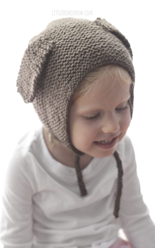 Little girl wearing brown knit bonnet with floppy puppy ears on the sides