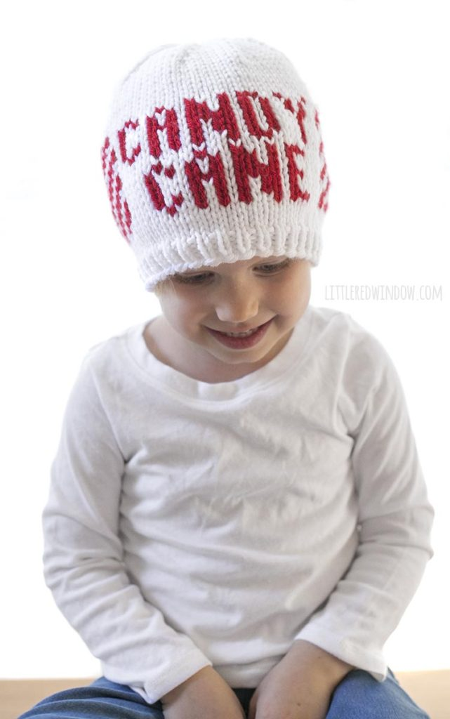 "Smiling toddler wearing a hat that says ""Candy Cane""!"