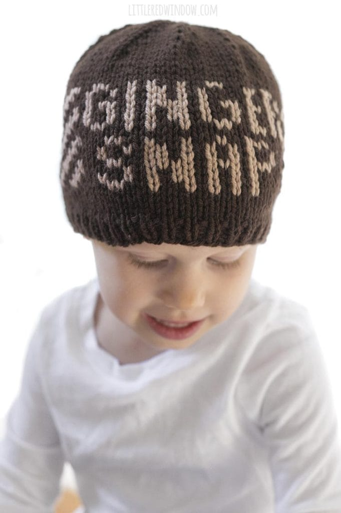 Adorable toddler wearing a knit hat that says